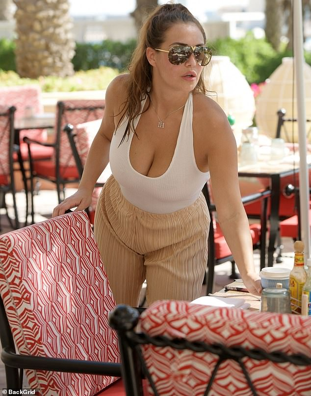 Alone time: The reality star, 26,completed her figure-hugging ensemble with ribbed wide-leg trousers in a champagne hueas she took a moment's break from her little girl Isla Elizabeth