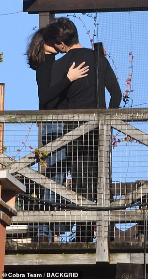 PDA: Standing atop a wooden bridge, the lovers were far from shy about packing on the PDA