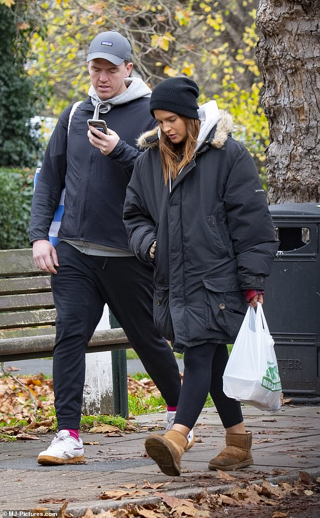 Outing: Binky Felstead bundled up in an oversized black coat as she headed out to a market in London with fiancé Max Darnton on Saturday