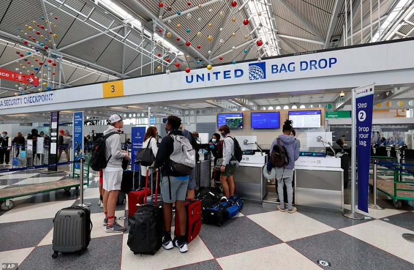CHICAGO: The recent weeks' soaring numbers of coronavirus cases in Illinois prompted Gov. J.B. Pritzker to reimpose harsher restrictions on social interaction. Pictured: Travelers at Chicago O'Hare on Friday