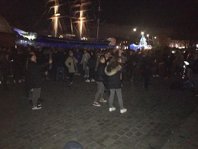 The masts of the historic British ship the Cutty Sark can be seen illuminated in the background in Greenwich