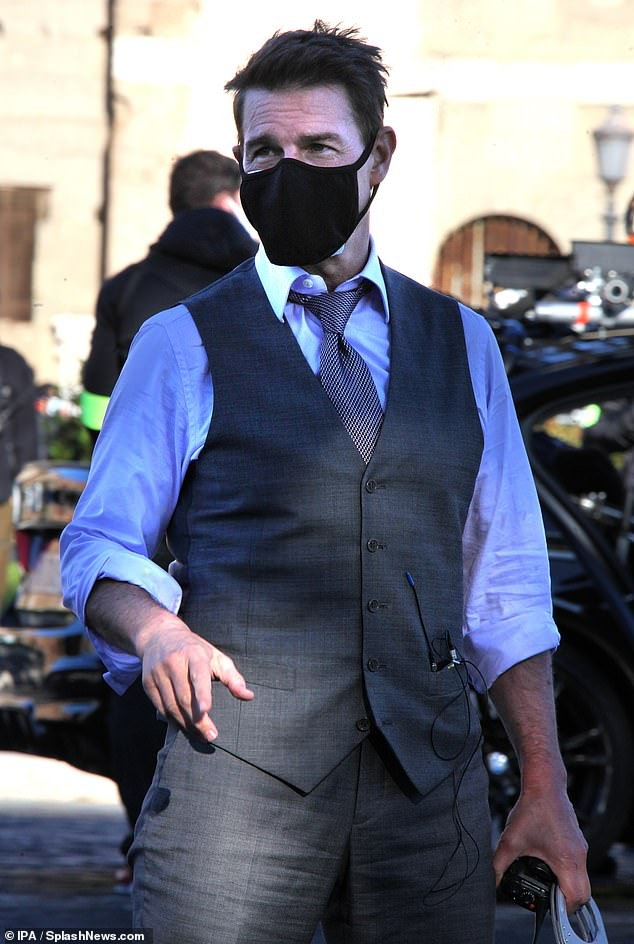 Hard at work: Tom Cruise cut a dapper figure as hetransformed into character Ethan Hunt by wearing a grey waistcoat while filmingMission Impossible 7 in Rome on Saturday