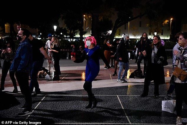 The regional government however has maintained the night-time curfew as well as the limits on movements of people into and out of the region. Pictured: Revellers on the streets of Barcelona tonight