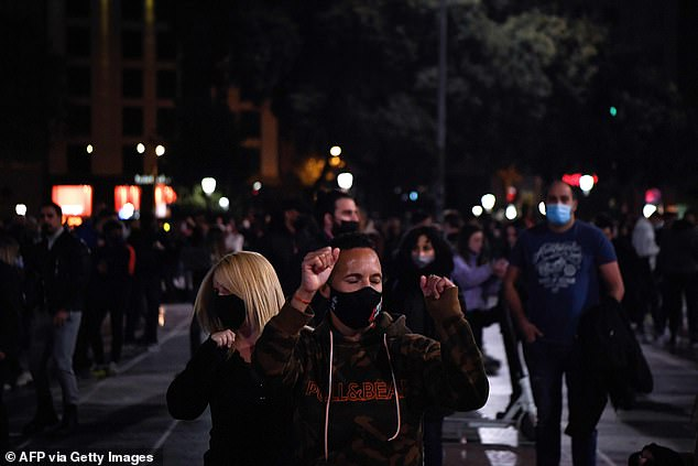 Like in the rest of Spain, the number of new Covid-19 infections has been falling in Catalonia. Pictured: Revellers took to the streets tonight