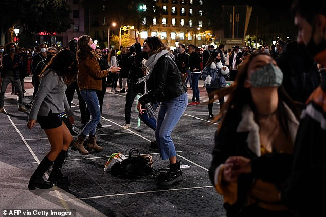 Locals who couldn't wait for the rules to change on Monday defiantly took to the streets of Barcelona tonight (pictured) - in breach of the 10pm lockdown curfew currently in place