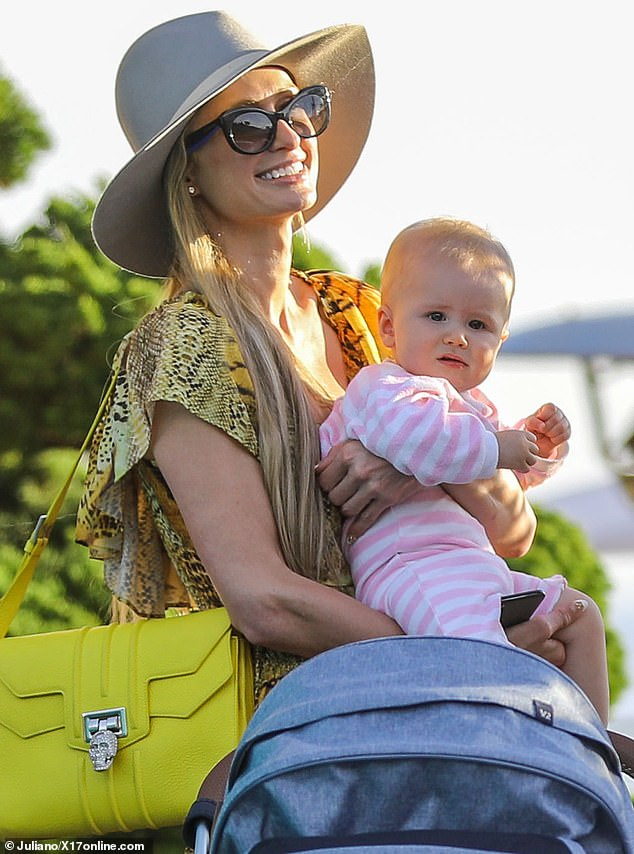 All smiles: Paris Hiltonwas all smiles Saturday in a floor-length animal-print dress with layered ruffles, as she held her adorable baby niece Milou during lunch with brother Barron Hilton and his wife Tessa at Nobu Malibu