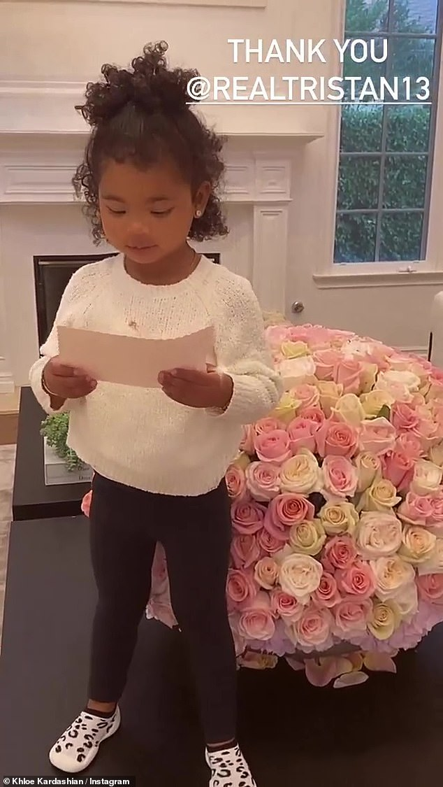 Stunning:True stood next to the arrangement of yellow, pink, and white roses atop a dark wood table in Khloe's living room