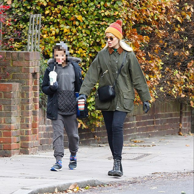 Back out: Holly Willoughby stepped out with her son Harry in London on Saturday as she was seen for the first time since her children's coronavirus scare