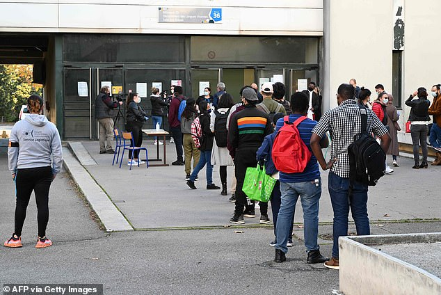 By contrast, the French guidelines prioritise high-risk occupations, including shop workers, school staff and transport workers. Pictured: Students line up outside a French school