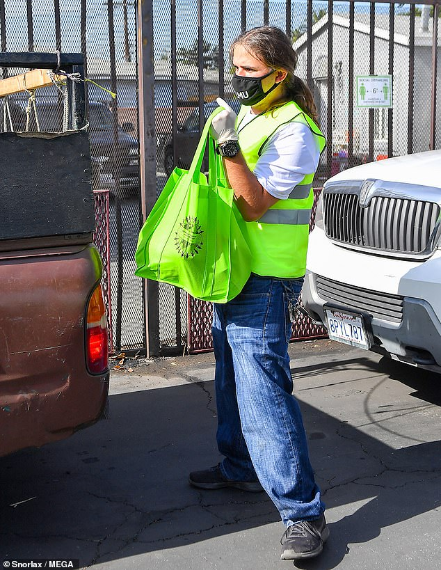 Dressed to work: Prince wore a reflective safety vest over a white graphic T-shirt, dark jeans and black sneakers