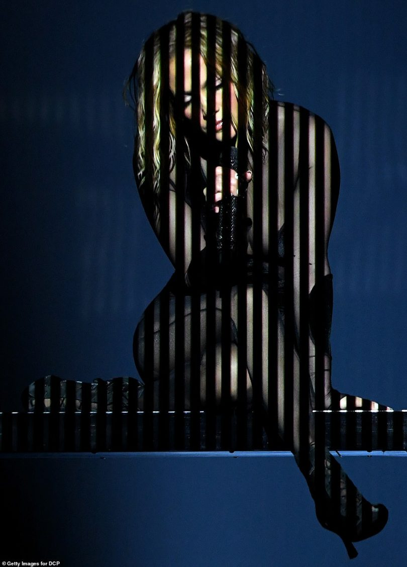 Seeing stripes: Striped lights lit her up, as she served body in a sheer black catsuit, while performing their track Pa Ti and Lonely