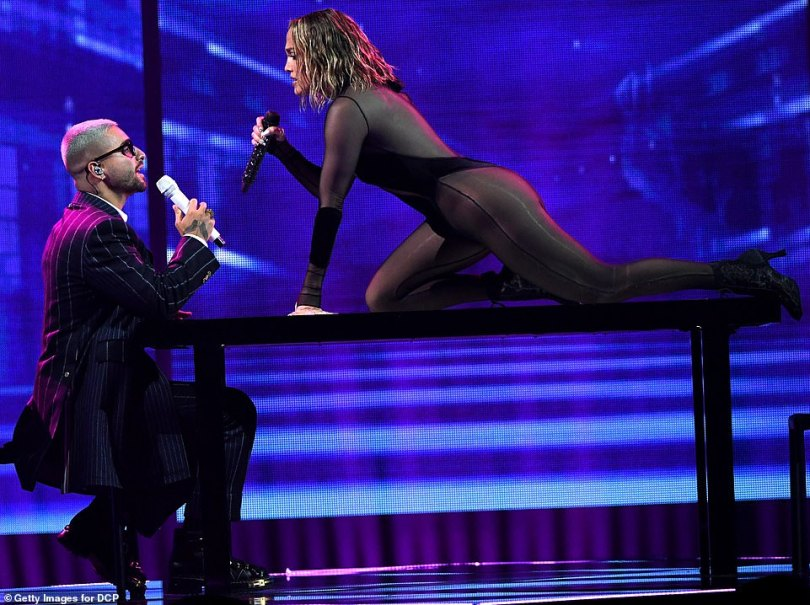 On trial: Lopez extended her killer legs as she stood atop a table, before she sat opposite Maluma, delivering a sexy musical interrogation