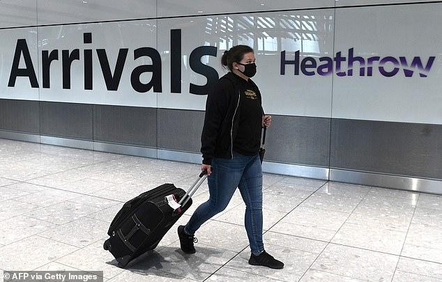 Passenger wears mask upon arrival at Heathrow Airport amid coronavirus pandemic