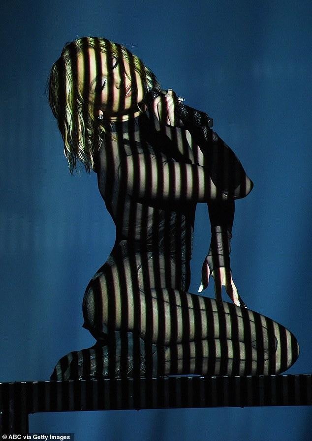 Pulsos acelerados: Lopez puso los pulsos acelerados en un escenario ahumado oscuro con un traje negro transparente mientras un foco en forma de cruz iluminaba su glamorosa taza.