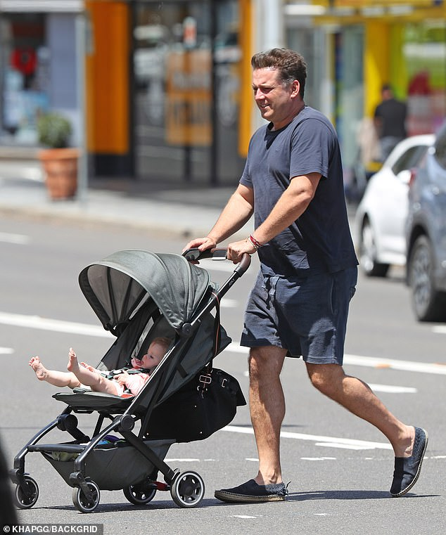 Walking it off: Karl pushed the stroller around the neighbourhood as his baby sat quietly inside