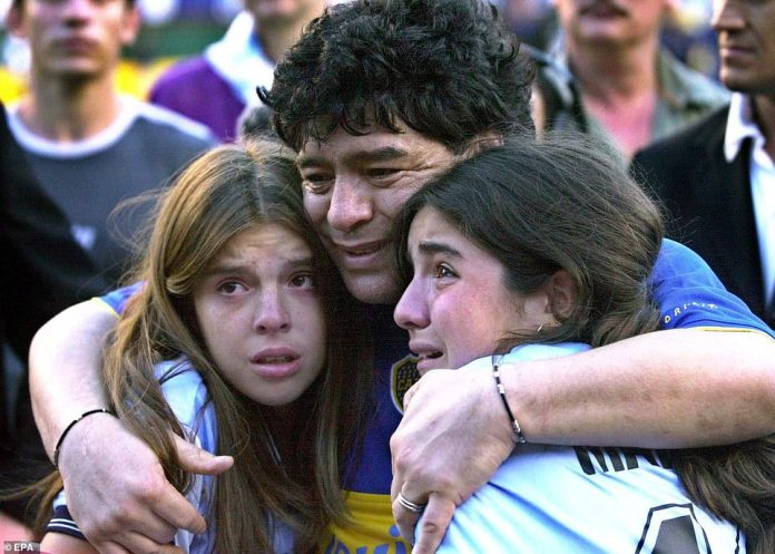 Maradona (C) embraces his daughters Dalma Nerea (L) and Gianinna Dinora (R) during a tribute match held in his honour at Boca Juniors Stadium in Buenos Aires, Argentina, in 2001