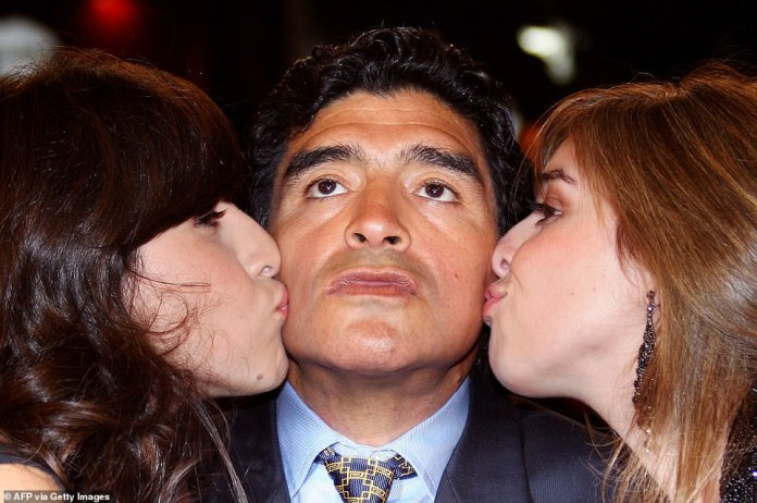 Argentinian football player Diego Maradona (C) is kissed by his daughters Giannina (L) and Dalma as he arrives to attend the screening of Serbian director Emir Kusturica's documentary film 'Maradona by Kusturica' at the 61st Cannes International Film Festival in Cannes in 2008