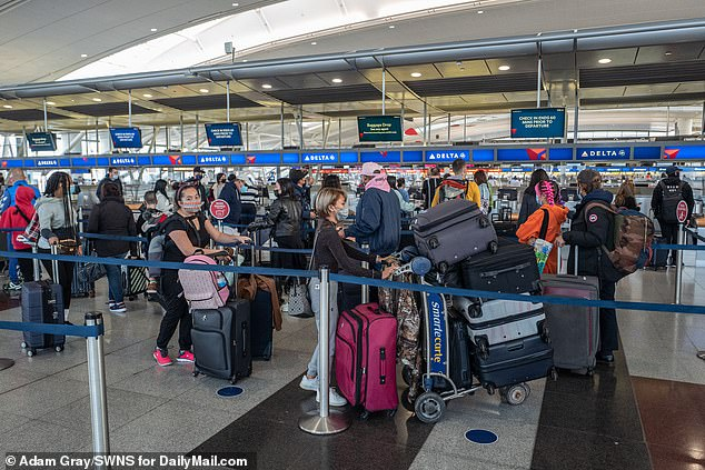 Travelers line up in JFK airport on Wednesday despite recommendations against travel
