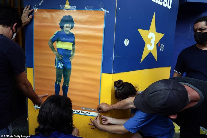 People hang a poster of Maradona outside the Boca Juniors stadium in Buenos Aires on Wednesday