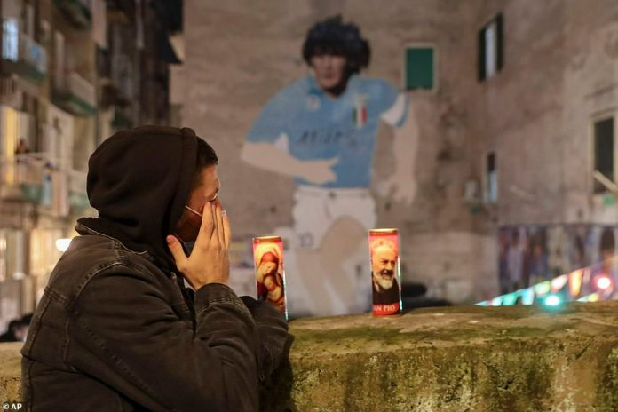 A man stands by two candles, one with an image of the Virgin Mary and the other St. Padre Pio, as a mural depicting soccer legend Diego Maradona is seen in background, in Naples, Italy