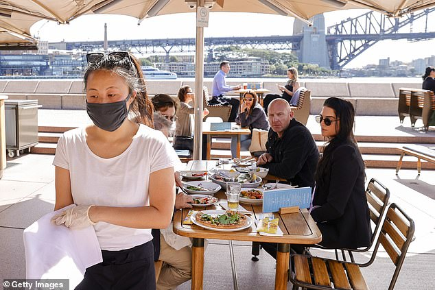A masked waitress attends customers at the Opera Bar, which is one of seven venues across Sydney that Moran runs. He said none of his venues will benefit from the easing of restrictions because they are all larger than 200 square metres