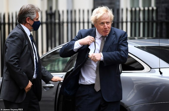 The PM wrestled with his mask as he exited his official car on returning from the Commons to No10 today