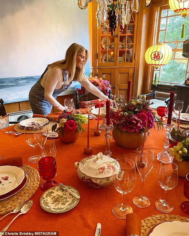 Stunning: The table had candles and flowers as she wore overalls over a white shirt
