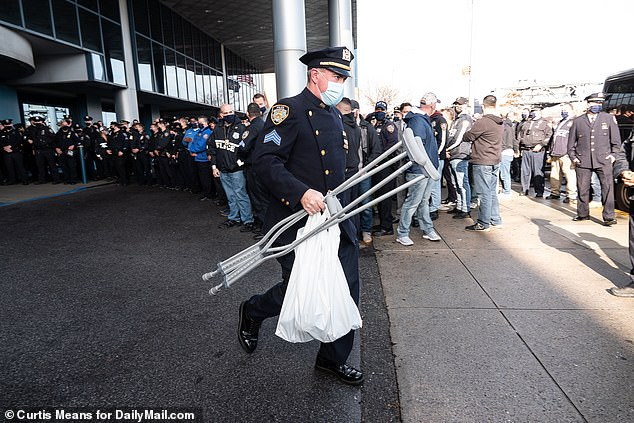 An officer carries crutches to the car for one of the wounded officers