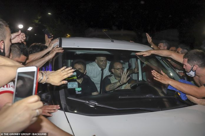 Diego Molina (pictured in a van transporting Maradona's body to his wake) has received death threats for desecrating the sporting great's body after he posed with one hand resting on Maradona's head and the other giving a thumbs up