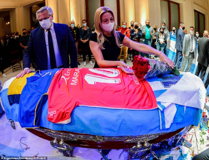 Argentine President Alberto Fernandez (L) and his partnet Fabiola Yanez paying tribute to the coffin of Argentine football legend Diego Maradona at the burning chapel in Casa Rosada presidential palace in Buenos Aires on November 26