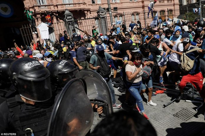People scuffle as riot police try to disperse them in front of the Casa Rosada presidential palace as they gather to mourn the death of soccer legend Diego Armando Maradona, in Buenos Aires