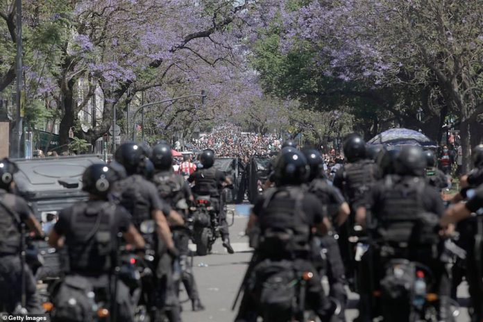 Riot police prepare for thousands of mourners heading down one of the grand avenues in Buenos Aires leading to the presidential palace