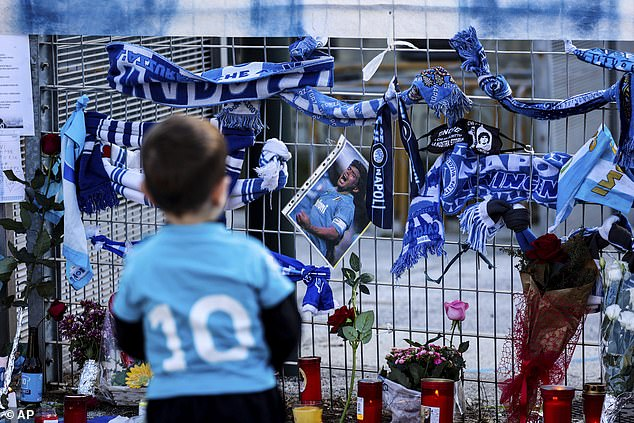 Scarves, photos and messages have also been left on the railings outside the ground
