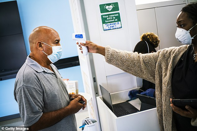 Airlines have been hammered by coronavirus fears. Pictured, a man gets his temperature checked during testing for COVID-19 before boarding his flight in Newark
