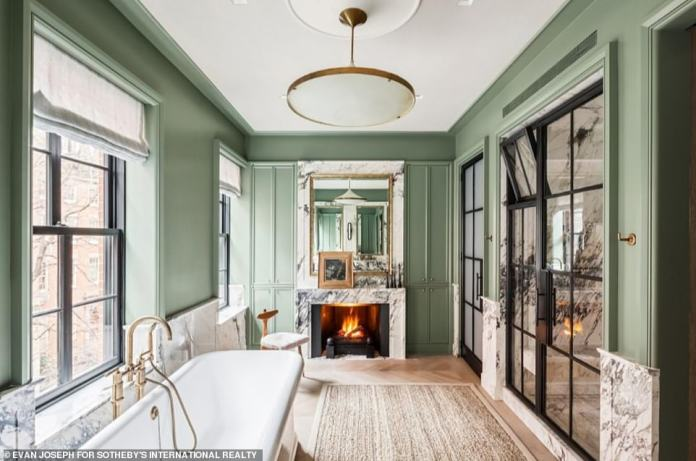 The home has been extensively remodeled, with all six of the building's full bathrooms given a full makeover. One of the lavish bathrooms, which comes complete with a claw bath, a fire place and marbled tiling, is pictured