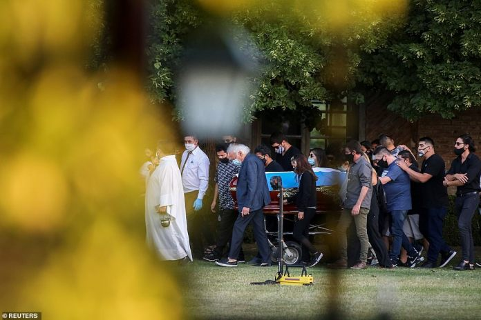 Friends and family carry the casket of soccer legend Diego Armando Maradona, at the cemetery in Buenos Aires, Argentina