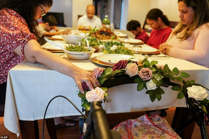 Deer Park, New York: Vivian Zayas holds onto the walker once belonging to her recently deceased mother Ana Martinez while her family prays before Thanksgiving dinner. Martinez died in April from COVID-19 at the age of 78
