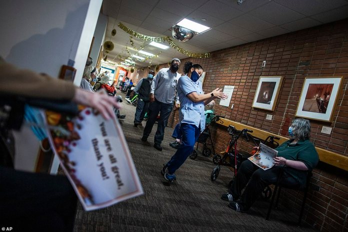 Bronx, New York: Nursing home residents hold signs as staff members walk by during a Thanksgiving celebration at the Hebrew Home at Riverdale on Thursday. The home also offered drive-up visits for families of residents struggling with celebrating the holiday alone
