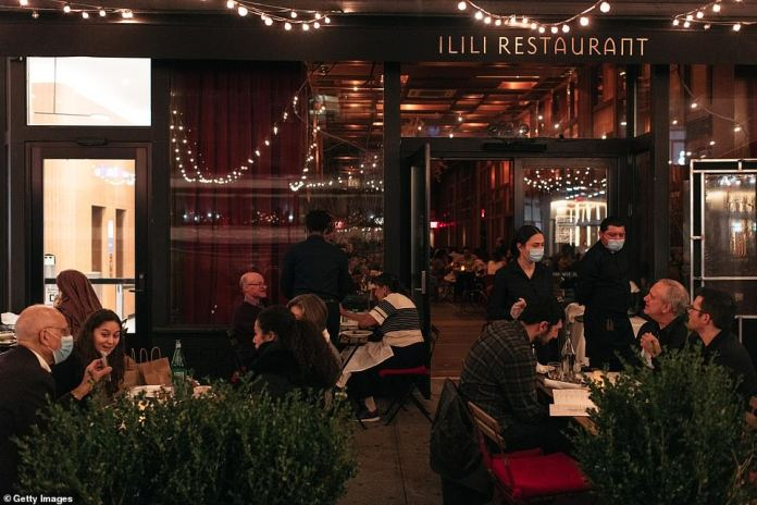 New York, New York: Families, couples, and friends dine out at a restaurant for Thanksgiving dinner
