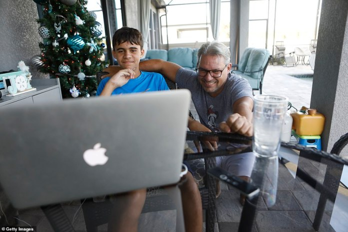 Valrico, Florida: Steve Collis and his youngest son Timmy talk with family in Delaware and Ohio on a Zoom call on Thursday