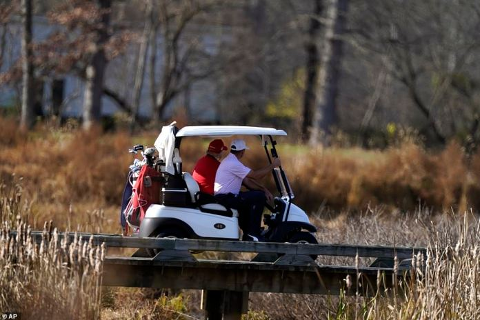 President Trump drives a golf cart on his course near Washington D.C.