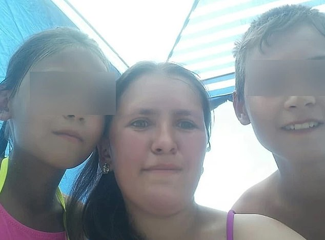 Gulnara Kostelnyuk, 31, was killed by a falling wooden beam in front of her 14-year-old son at their burning home in Yakutsk, east Russia, on Wednesday after she saved her five children (pictured with her two of her children)