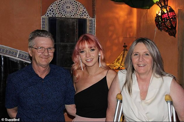 The young woman, centre, had to move back in with her parents, also pictured, after her vision deteriorated to the point where she couldn't drive