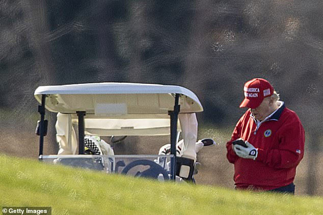 President Trump checks his phone while on the golf course