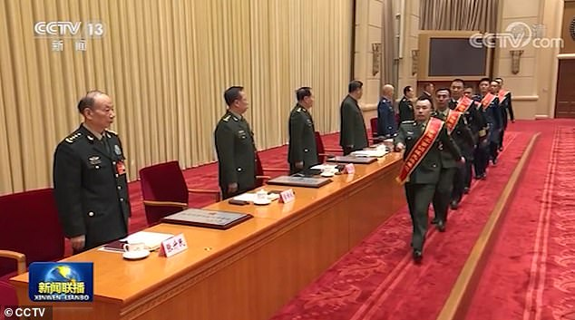 Xi called for the forces to maintain the fighting spirits of 'fearing neither hardship nor death', adding that the country's military development and situation entered 'a new era'. The screenshot from CCTV shows a group of soldiers being awarded by President Xi and officials