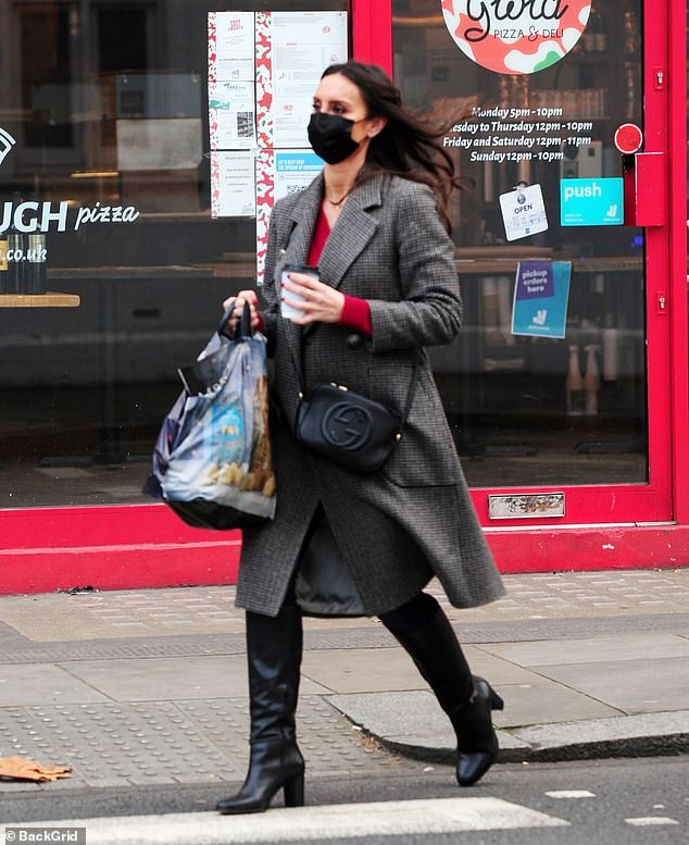 Sleek:The Loose Women panellist looked effortlessly stylish as she strolled along in knee-high boots while keeping warm with a long grey checked coat