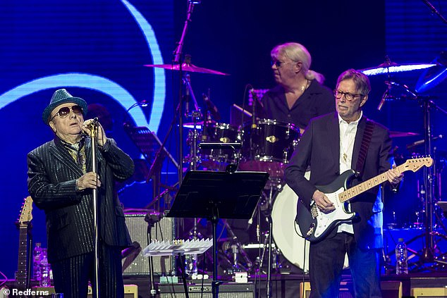Music legends Eric Clapton and Van Morrison have been slammed on Twitter for joining forces to record a new song that is critical of COVID-19 lockdowns. The pair, both 75, are pictured above performing in London in March before coronavirus restrictions were enforced