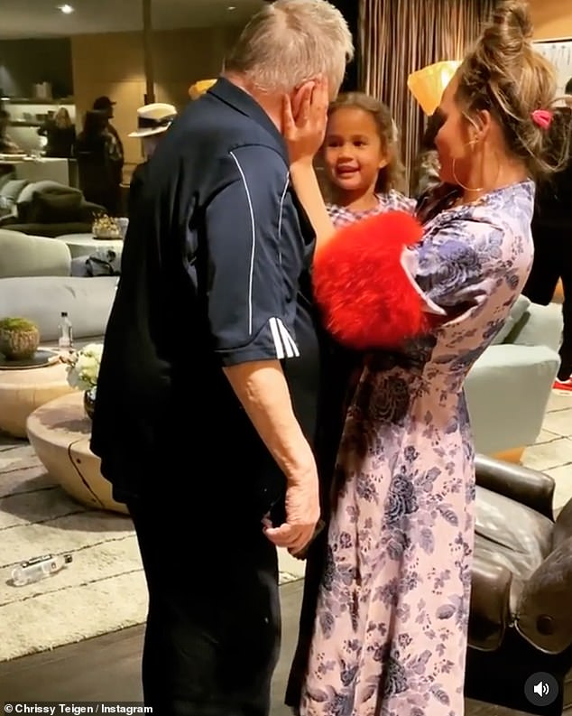 Family love:In the adorable clip, the TV personality and model, 34, held her little girl in her arms while embracing her father and planting a kiss on his cheek