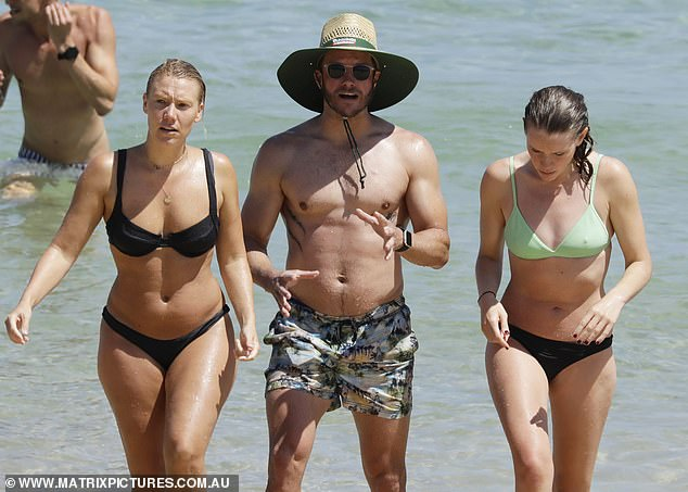 Eye-catching look: Looking every inch the true blue Aussie, Luke wore a pair of colourful board shorts and a sunhat emblazoned with the Bunnings Warehouse logo