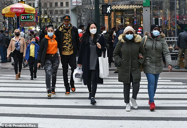 Residents wear face masks as they shop in Herald Square in Midtown Manhattan on November 27 (pictured), where strict restrictions are still in place